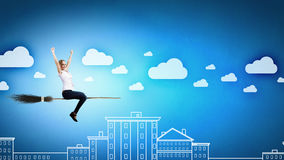 Girl on broom. Young girl in casual flying on broom high in sky royalty free stock photos