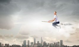 Girl on broom. Young girl in casual flying on broom high in sky royalty free stock photography