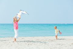 Girl with brother on beach playing with a kite Stock Image