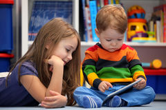 Girl and brother fun using a digital tablet computer Royalty Free Stock Images