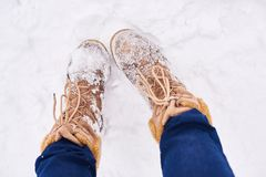 Girl brown boots standing on snow. Pair brown boots in white fresh snow, girl wears jeans and walks outdoor royalty free stock photo
