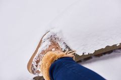 Girl brown boots standing on snow. Pair brown boots in white fresh snow, girl wears jeans and walks outdoor stock images