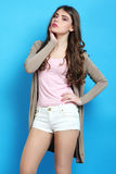 Girl in brown cardigan. Stylish girl in brown cardigan on blue background Stock Image