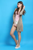Girl in brown cardigan. Stylish girl in brown cardigan on blue background Royalty Free Stock Images