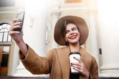 Girl in a brown coat a brown hat is walking and posing in the city interiors. The girl is smiling, checking her. Smartphone and drinking coffee from take away Stock Images