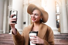 Girl in a brown coat a brown hat is walking and posing in the city interiors. The girl is smiling, checking her. Smartphone and drinking coffee from take away Stock Photos
