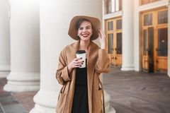 Girl in a brown coat a brown hat is walking and posing in the city interiors. The girl is smiling, checking her smartphone and dri Stock Photos