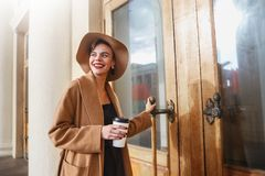 Girl in a brown coat a brown hat is walking and posing in the city interiors. The girl is smiling, checking her smartphone and dri Royalty Free Stock Photography