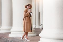 Girl in a brown coat a brown hat is walking and posing in the city interiors. The girl is smiling, checking her smartphone and dri Stock Image