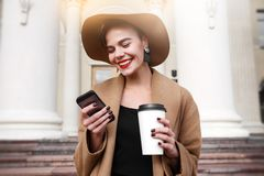 Girl in a brown coat a brown hat is walking and posing in the city interiors. The girl is smiling, checking her. Smartphone and drinking coffee from take away Stock Photography
