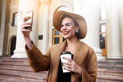Girl in a brown coat a brown hat is walking and posing in the city interiors. The girl is smiling, checking her. Smartphone and drinking coffee from take away Royalty Free Stock Image