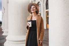 Girl in a brown coat a brown hat is walking and posing in the city interiors. The girl is smiling, checking her smartphone and dri Royalty Free Stock Photos