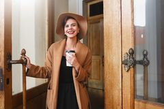 Girl in a brown coat a brown hat is walking and posing in the city interiors. The girl is smiling, checking her smartphone and dri Royalty Free Stock Image