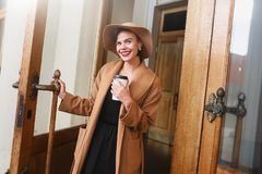 Girl in a brown coat a brown hat is walking and posing in the city interiors. The girl is smiling, checking her smartphone and dri Royalty Free Stock Photo