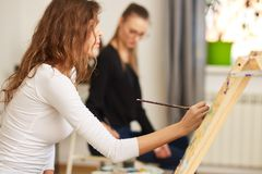 Girl with brown curly hair dressed in white blouse paints a picture at the easel in the drawing school stock images