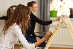Girl with brown curly hair dressed in white blouse paints a picture at the easel in the drawing school royalty free stock images