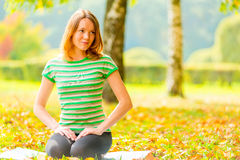 Girl with brown eyes resting on the grass. And looking to the side royalty free stock image