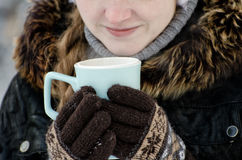 Girl in the brown gloves holding a blue mug of tea, part of the face, close-up Royalty Free Stock Photography