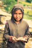 Girl in brown hood in Nepal. Dolpo, Nepal - circa June 2012: Young native girl in brown sweatshirt and hood holds cake in Dolpo, Nepal. Documentary editorial Stock Photography