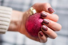 Girl with brown manicure nails polish gel on finger nail holding red Christmas ball. Beautiful woman with brown manicure nails polish gel on finger nail holding stock photography
