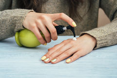 Girl in brown sweater with yellow manicure applying hand cream, Stock Image
