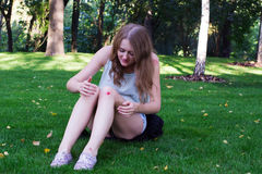 Girl with a bruise on her knee. Sitting on the grass and looking at the wound Royalty Free Stock Image