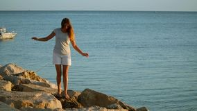 Girl walking on rocks stock footage