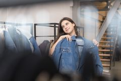 The girl in the clothing store chooses a denim jacket, chose and pressed to her. stock image