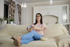 Girl brunette with glasses with popcorn playing in video games s royalty free stock image