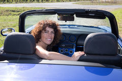 Girl brunette, happy in blue cabriolet driving on road trip Stock Image