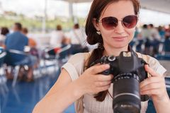 The girl the brunette photographs the camera. The girl the brunette the photographer in a summer blouse and sunglasses photographs the digital camera stock photo