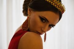 Girl brunette in a red dress with beautiful hairstyle,. Earrings of beads and a crown on her head and bright makeup. Female style. Mysterious woman Royalty Free Stock Photos