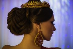 Girl brunette in a red dress with beautiful hairstyle,. Earrings of beads and a crown on her head and bright makeup. Female style. Mysterious woman. Blue light Stock Images