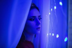 Girl brunette in a red dress with beautiful hairstyle,. Earrings of beads and a crown on her head and bright makeup. Female style. Mysterious woman. Blue light Stock Photo