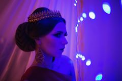 Girl brunette in a red dress with beautiful hairstyle,. Earrings of beads and a crown on her head and bright makeup. Female style. Mysterious woman. Blue light Royalty Free Stock Photo