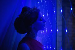 Girl brunette in a red dress with beautiful hairstyle,. Earrings of beads and a crown on her head and bright makeup. Female style. Mysterious woman. Blue light Royalty Free Stock Images