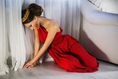 Girl brunette in a red dress with beautiful hairstyle. Earrings of beads and a crown on her head and bright makeup. Female style. Mysterious woman Royalty Free Stock Photo
