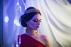 Girl brunette in a red dress with beautiful hairstyle,. Earrings of beads and a crown on her head and bright makeup. Female style. Mysterious woman. Blue light Royalty Free Stock Photography