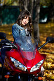 Girl brunette with a red motorcycle Royalty Free Stock Images