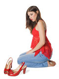 Girl brunette and red sandals. Attractive young girl to apply red lacquered sandals Stock Image