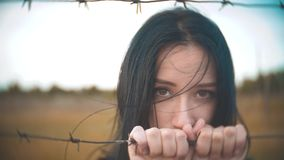 Girl brunette refugee behind barbed wire camp lifestyle slow motion video. the concept of freedom is upset Woman hands. Girl brunette refugee behind barbed wire stock video footage