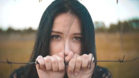 Girl brunette refugee behind barbed wire camp slow motion video. the concept of freedom is upset Woman hands and barbed. Girl brunette refugee behind barbed wire stock footage