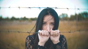 Girl brunette refugee behind barbed wire camp slow motion video. the concept of freedom is upset Woman lifestyle hands. Girl brunette refugee behind barbed wire stock video footage