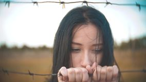 Girl brunette refugee behind barbed wire lifestyle camp slow motion video. the concept of freedom is upset Woman hands. Girl brunette refugee behind barbed wire stock footage