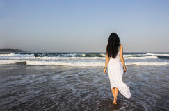 Girl brunette in white dress entering the Indian Ocean. Young beautiful woman brunette with long dark hair and gold bracelets  in white dress entering the Royalty Free Stock Photos