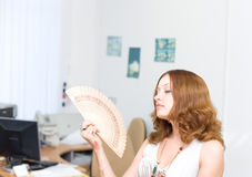 Girl brush away face by fan #1. Girl in office brush away face by fan Stock Photos