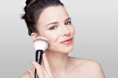 Girl and a brush. Beautiful woman holding a face brush against her face Royalty Free Stock Images