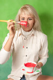 Girl with a brush and a cup full of red paint Stock Image