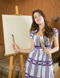 Girl with brush near easel Royalty Free Stock Images