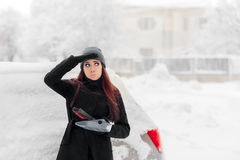 Girl with Brush and Shovel Removing Snow from the Car Stock Photography